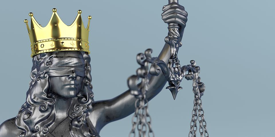 Image of Justitia, goddess of justice, as an iron statue with a golden crown on her head.