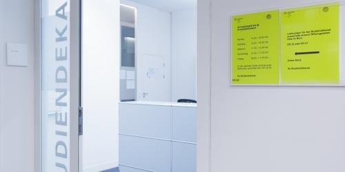 Blick auf den Eingangsbereich des Studiendekanats der Juristischen Fakultaet mit der Eingangstuer im Zentrum und den auf einen gelben Zettel angezeigten Oeffnungszeiten rechts.
